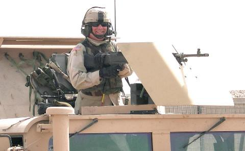 Photograph of an American soldier manning a machine gun on his Humve in Iraq, taken by an American soldier taken by an American soldier of C Co, 1/252 Army Reserve Battalion.  Logo for the M203.com presentation entitled Warrior.