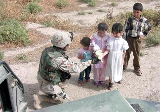 Photograph of an American soldier giving gifts to children in Iraq, taken by an American soldier of C Co, 1/252 Army Reserve Battalion . Logo for the M203.com presentation entitled Why.