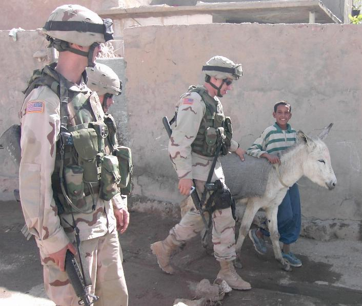 Photograph of teenager and his donkey walking with American soldiers in Iraq. Photograph by an American soldier of C Co, 1/252 Army Reserve Battalion.
