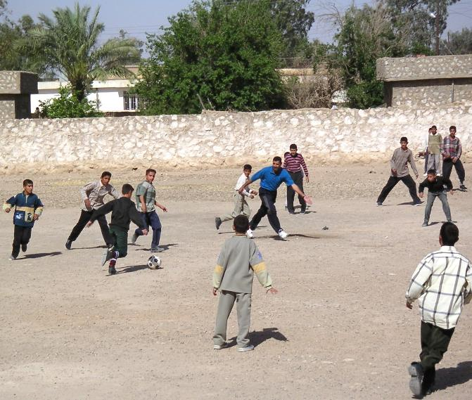 Photograph of Iraqi children playing kick ball. Photograph by an American soldier of C Co, 1/252 Army Reserve Battalion.