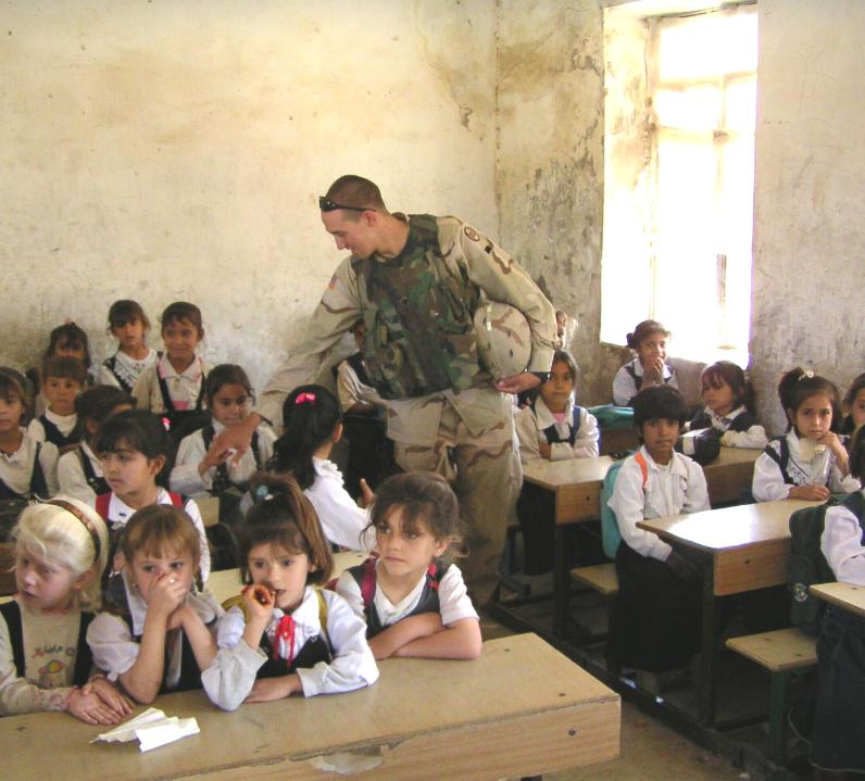 Photograph of Iraqi children in their class room and an American soldier visiting them. Photograph by an American soldier of C Co, 1/252 Army Reserve Battalion.