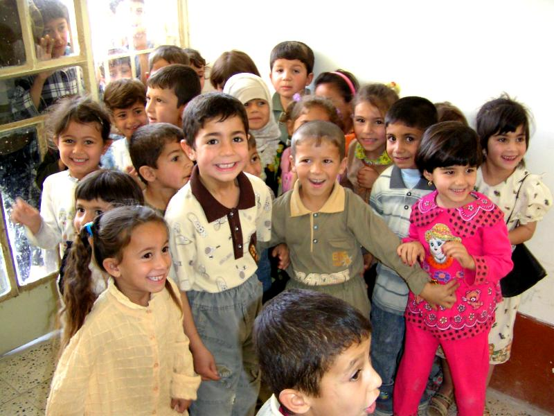 Photograph of Iraqi children in their class room smiling into the camera. Photograph by an American soldier of C Co, 1/252 Army Reserve Battalion.