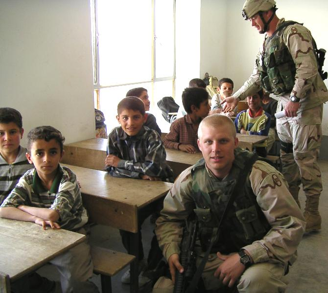 Photograph of Iraqi children in their class room smiling into the camera along with an American soldier who is visiting them. Photograph by an American soldier of C Co, 1/252 Army Reserve Battalion.