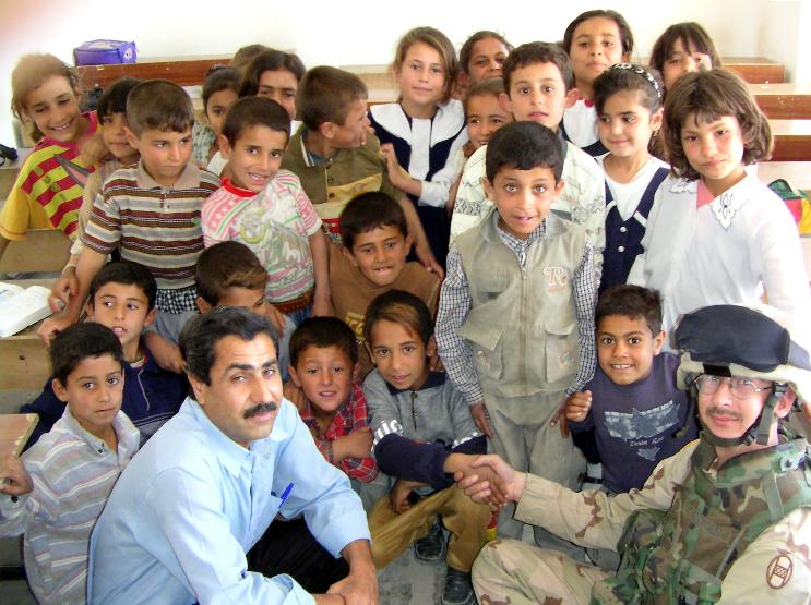 Photograph of Iraqi children in their class room with their teacher and an American soldier who is shaking the hand of one young boy. Photograph by an American soldier of C Co, 1/252 Army Reserve Battalion.