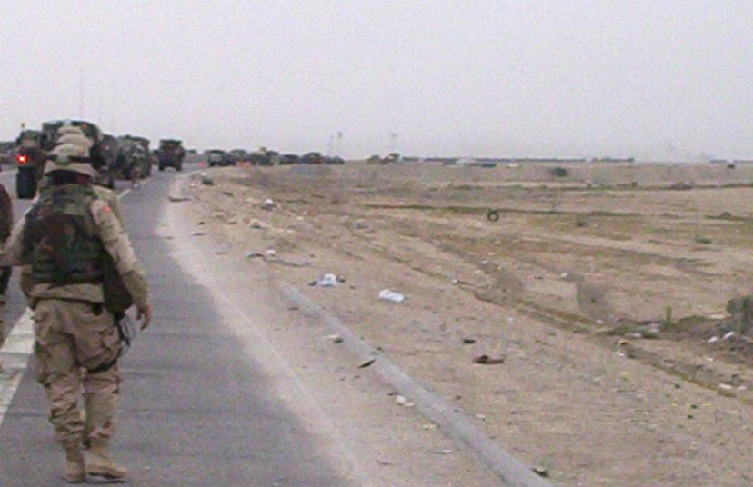Photograph of a long line of military vehicles and men marching down a road in Iraq. Photograph by an American soldier of C Co, 1/252 Army Reserve Battalion.
