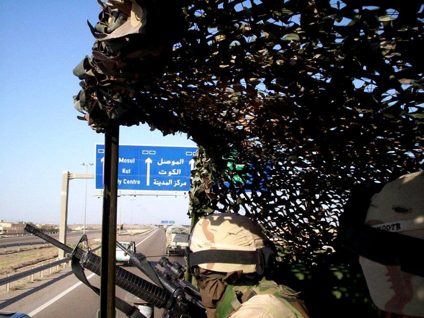 Photograph of an Iraqi highway sign from the point of view of a soldier ridding in the Humve. Photograph by an American soldier of C Co, 1/252 Army Reserve Battalion.