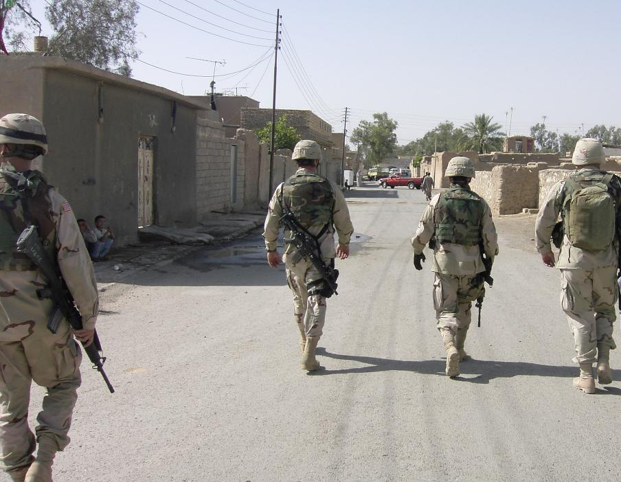 Photograph of four American soldiers walking away from the camera, down a street in Iraq. Photograph by an American soldier of C Co, 1/252 Army Reserve Battalion.